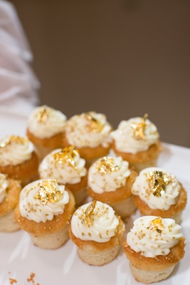 Cupcakes with white frosting and gold sprinkles at wedding