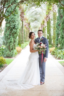Bride in strapless wedding dress sheer side cutouts groom in grey suit florida wedding