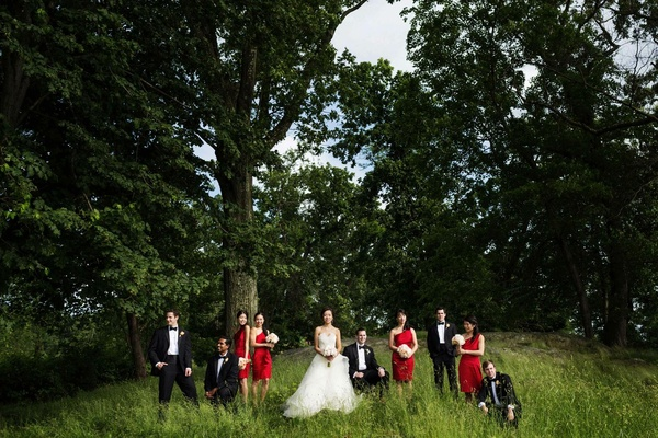Bride in a Monique Lhuillier gown, groom and groomsmen in a black tuxedos, and bridesmaids in red