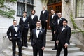 Groom and groomsmen in tuxedo suits with black bow ties white pocket squares boutonniere