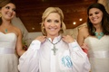 Bride putting on necklace with turquoise cross with bridesmaid necklaces