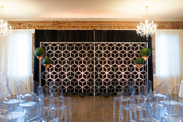a contemporary style ceremony space including geometric backdrop spherical arrangements ghost chairs