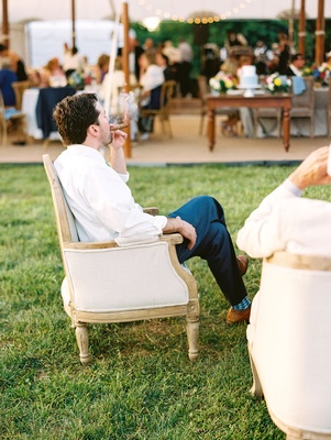 Male guest having cigar at cigar station lounge area by tent wedding reception