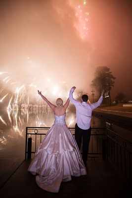 Bride and groom holding hands with ball gown firework show over water in distance over bayou