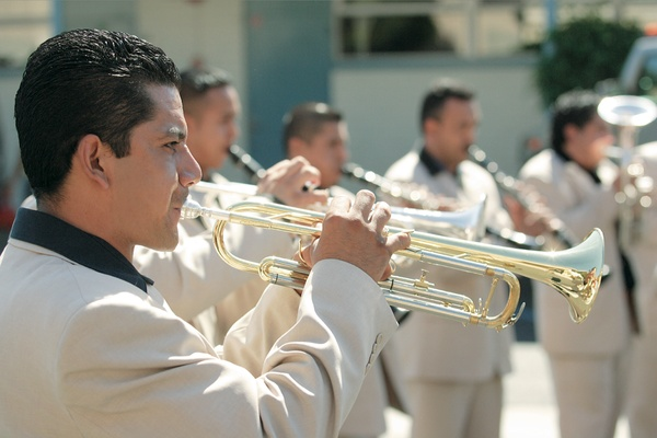 Man playing trumpet in tan suit with black shirt