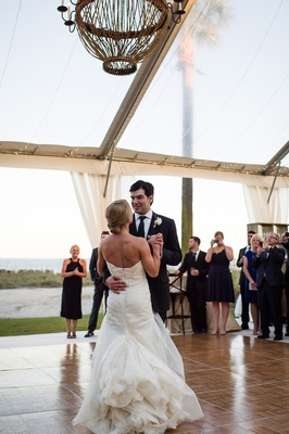 Bride and groom dancing beneath clear reception tent