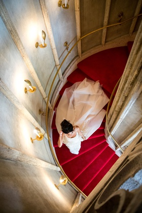 wedding portrait aerial shot of bride in wedding dress walking down red carpet spiral stairs