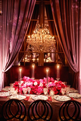 wedding reception table chandelier drapery pink red rose flowers butterfly china plates taper candle