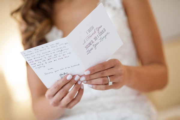 bride with white manicure reading love letter card from groom on wedding day