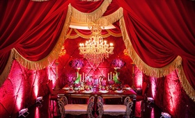 beauty and the beast inspired table setting framed by red theater curtains