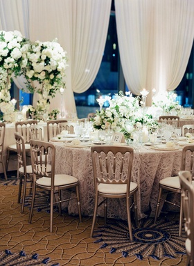 Wedding reception silver chairs around round tables green and white centerpieces drapery Chicago