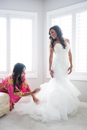 bride in monique lhuillier mermaid wedding dress, maid of honor in robe fluffs bridal gown