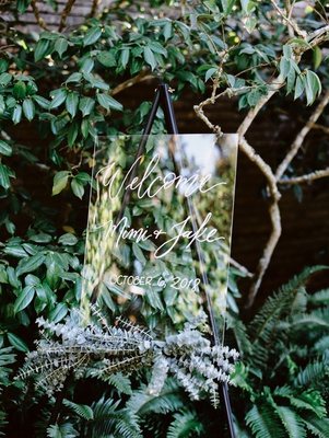 wedding lucite welcome sign on black easel with eucalyptus at base