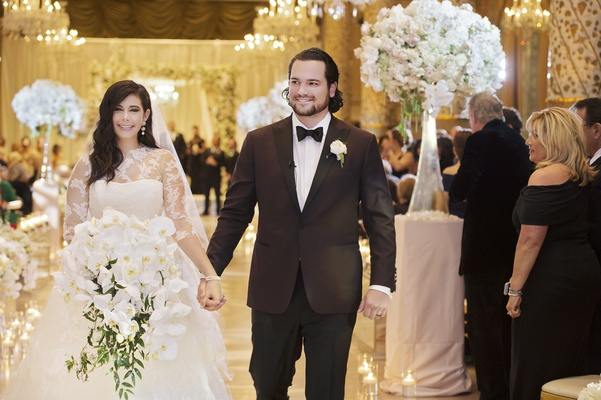 bride in vera wang ball gown and full orchid bouquet holding hands during recessional with groom
