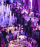 Guests at dinner service under chandeliers and purple lighting