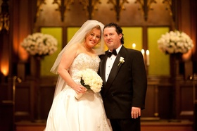 Bride and groom smile at church ceremony altar