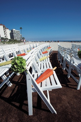 rows of white wooden chairs with umbrellas at beach ceremony