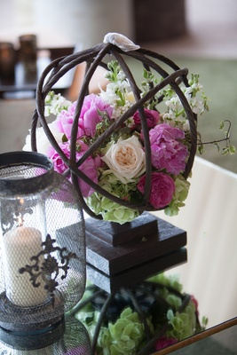 pink flower, cream rose, greenery in branch sphere on table at wedding
