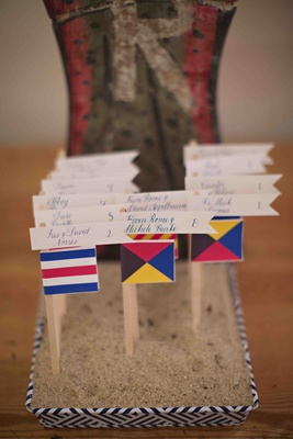 Seating cards in sand box on top of nautical boat flags