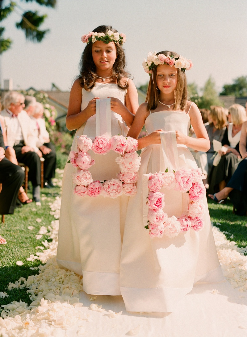 Flower girls holding pink rose frame down aisle