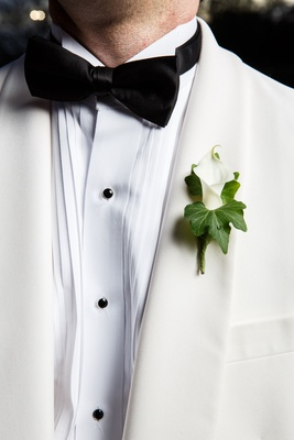 Wedding on new year's eve ideas groom in tuxedo white jacket black bow tie calla lily boutonniere