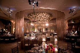 ballroom reception with pale pink lighting and candles
