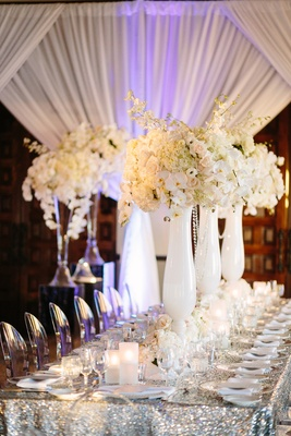 ghost chairs, silver sequin linens, white vases, orchid and rose centerpieces