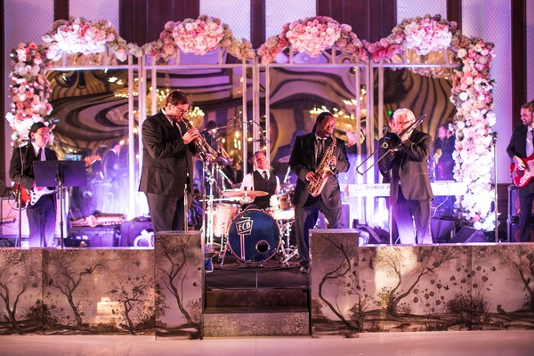 Live band performs at reception on stage with mirrors blush pink white flower decorations