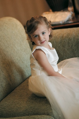 Little girl in ivory dress with hair pulled back