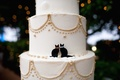 Round wedding cake with gold details and kitten decor