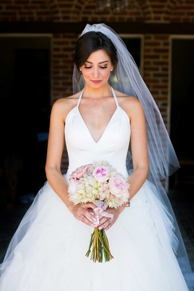 bride in white tulle ball gown with plunging halter neckline looking down at blush ivory bouquet