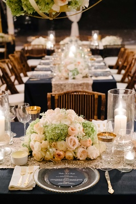 Navy blue linen on long table wedding reception hydrangea rose centerpiece low gold charger glasses
