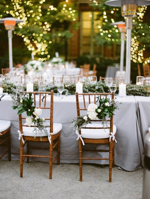natural chiavari chairs with arrangements of white flowers and greenery