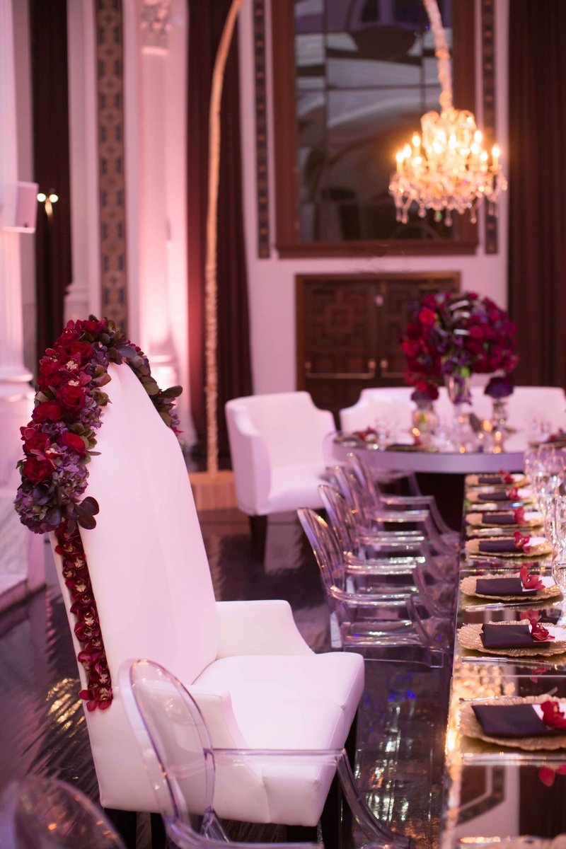 Bride and groom bench with tall back and garland of red and purple flowers at head table