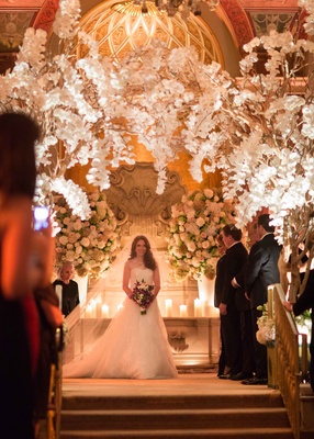 Bride holding purple white bouquet down aisle with orchid branches overhead