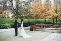 Bride in lace long sleeve wedding dress taps groom's shoulder in Chicago park
