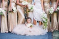 Flower girl in tulle dress gown in front of bridesmaids during photos little bouquet white flowers
