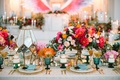 bold floral arrangements white linen gold chargers plateware rainbow colors wedding reception