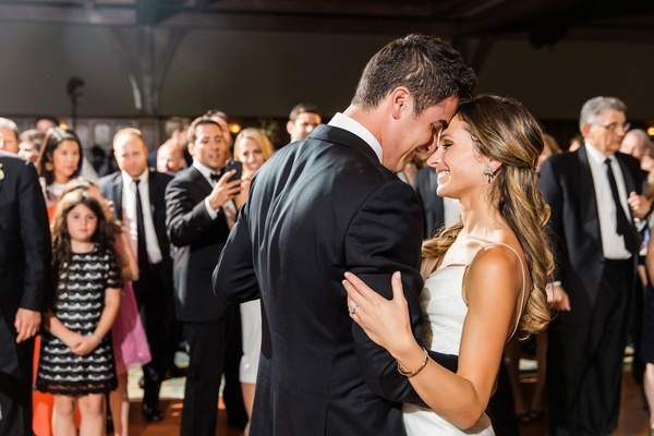Guests watching as bride and groom touch foreheads smile during first dance wedding reception