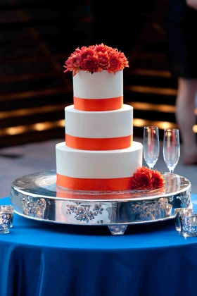 Wedding cake on silver stand on blue table with orange ribbons