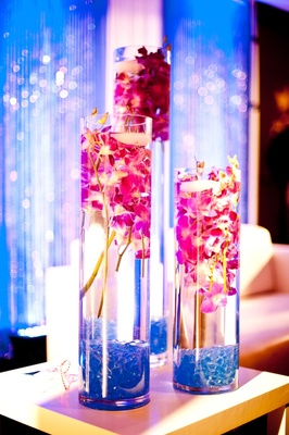 Cylindrical vases filled with pink orchids and candles
