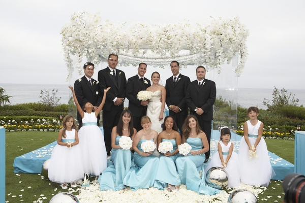 turquoise and white bridal party in front of white flower chuppah