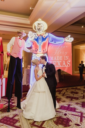 wedding reception after party bride groom kiss big tex neon sign and tall stilt walker
