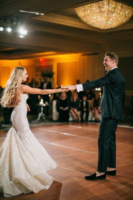 Groom smiles as he dances with his bride in Berta wedding dress bustle for dancing chandelier