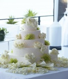Five layer white basket weave cake with roses and green protea