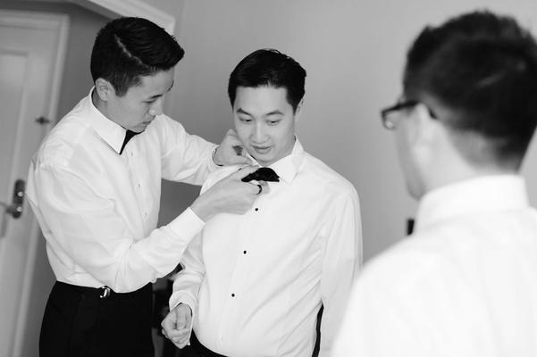 groomsmen help groom tie bow tie