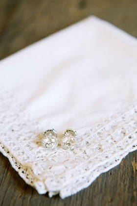 Bride's diamond pave stud earrings on handkerchief with lace trim
