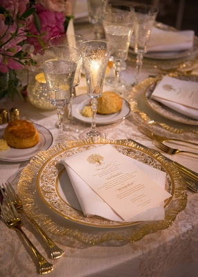 gold charger with white china place and gold designs