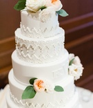 White wedding cake with filigree details and monogram and wedding date fondant blends into cake