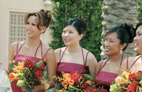 Bridesmaids with fall colored bouquets in red dresses